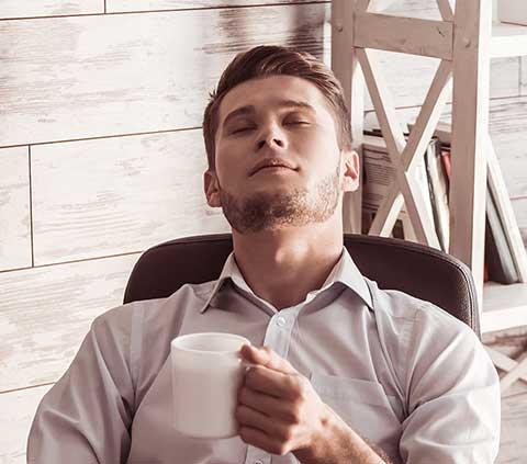 Mann sitzt mit einem Kaffee und geschlossenen Augen auf seinem Bürostuhl